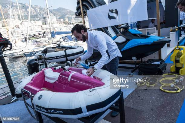An employee cleans a DarthCraft water sled in the 'tenders and toys' display area during the Monaco Yacht Show in Port Hercules Monaco on Wednesday...