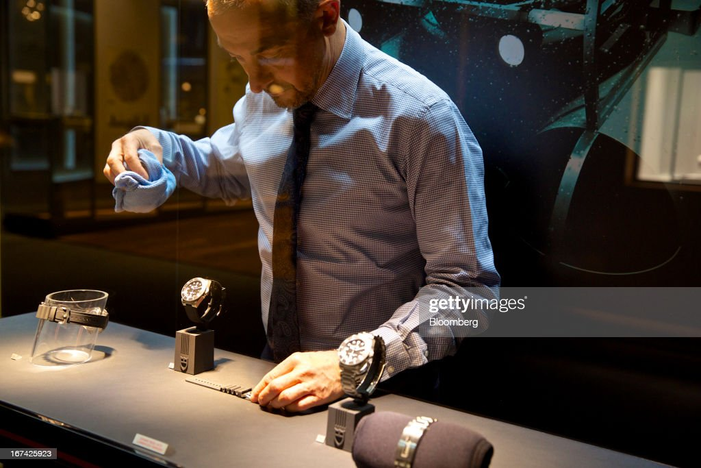 An employee cleans a display of wristwatches at the Tudor booth during the Baselworld watch fair in Basel, Switzerland, on Thursday, April 25, 2013. The annual fair attracts 2,000 companies from the watch, jewelry and gem industries to show their new wares to more than 100,000 visitors. Photographer: Gianluca Colla/Bloomberg via Getty Images