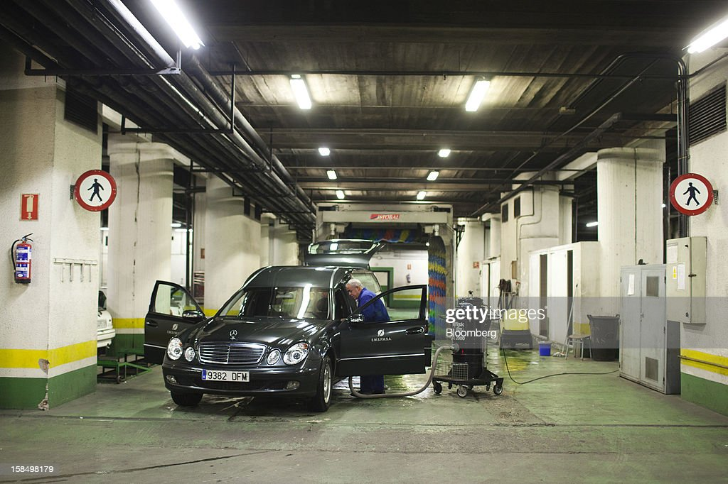 An employee cleans a funeral hearse in the parking bay of the Empresa Mixta de Servicios Funerarios de Madrid SA funeral parlour in Madrid, Spain, on Monday, Dec. 17, 2012. Spain, responding to street protests and reports of suicides linked to foreclosures, introduced rules to help protect families from eviction, increasing the risk of creditor losses and weakening an already fragile banking system. Photographer: Angel Navarrete/Bloomberg via Getty Images