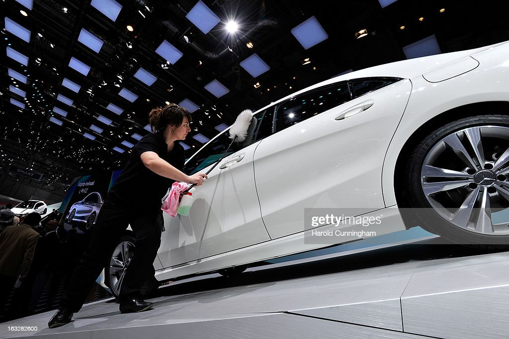 An employee cleans a Mercedes-Benz car during the 83rd Geneva Motor Show on March 6, 2013 in Geneva, Switzerland. Held annually with more than 130 product premiers from the auto industry unveiled this year, the Geneva Motor Show is one of the world's five most important auto shows.