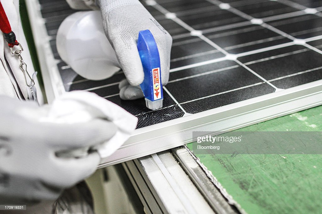 An employee cleans a solar panel before packaging at the Tata Power Solar Systems Ltd. manufacturing plant in Bangalore, India, on Tuesday, June 11, 2013. Tata Groups solar unit is expanding its business building plants for customers, forecasting that offices and factories will be paying more for grid power than solar by 2016 in most Indian states. Photographer: Dhiraj Singh/Bloomberg via Getty Images