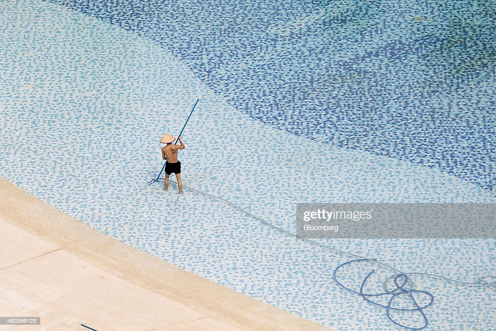 An employee cleans a swimming pool at Mission Hills Resort Haikou in Haikou, Hainan Province, China, on Saturday, April 5, 2014. The yuan is poised to recover from declines that have made it Asias worst-performing currency as China seeks to prevent an exodus of capital that would threaten economic growth, according to the most accurate forecasters. Photographer: Brent Lewin/Bloomberg via Getty Images