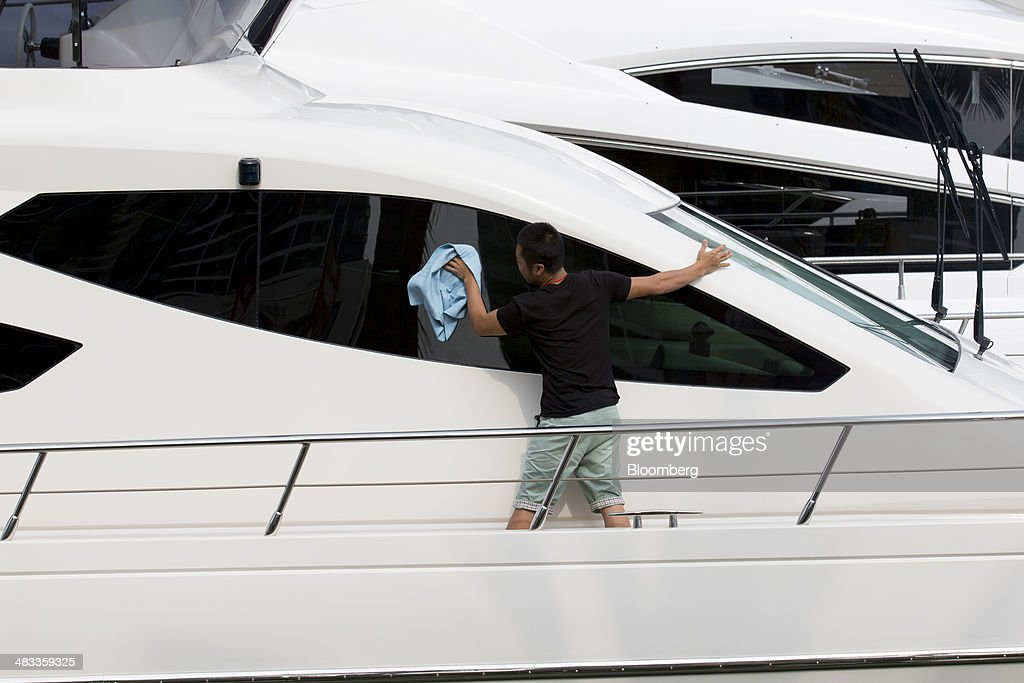 An employee cleans a yacht at the Visun Royal Yacht Club in the Sanya Bay district of Sanya, Hainan Province, China, on Monday, April 7, 2014. The yuan is poised to recover from declines that have made it Asia's worst-performing currency as China seeks to prevent an exodus of capital that would threaten economic growth, according to the most accurate forecasters. Photographer: Brent Lewin/Bloomberg via Getty Images
