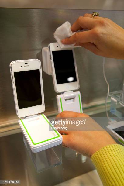 An employee cleans an Apple Inc iPhone connected to a Leitz smartphone charger operated by Esselte Leitz GmbH Co KG ahead of the opening of the IFA...