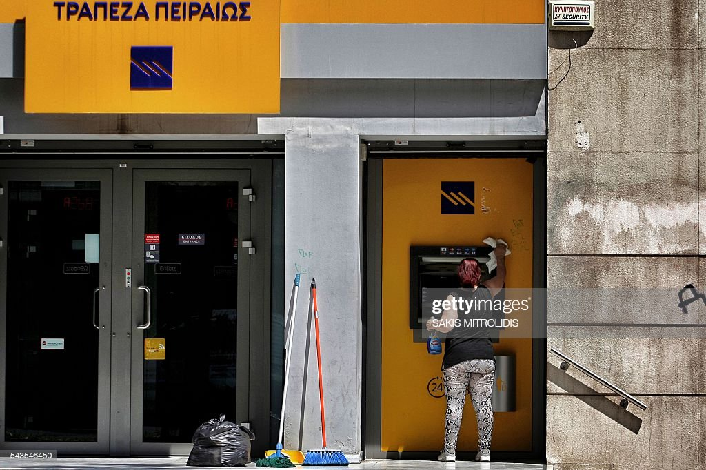 An employee cleans an ATM machine outside of a bank in Thessaloniki on 29 June, 2016. For a year the Greeks had to get used to not being able to withdraw more than 420 euros per week from the bank, a measure decided by credit control in full emergency which contributed to the stagnation of the economy. / AFP / SAKIS