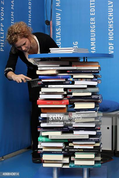 An employee cleans books at the 2014 Frankfurt Book Fair on October 8 2014 in Frankfurt Germany The 2014 fair which is among the world's largest book...
