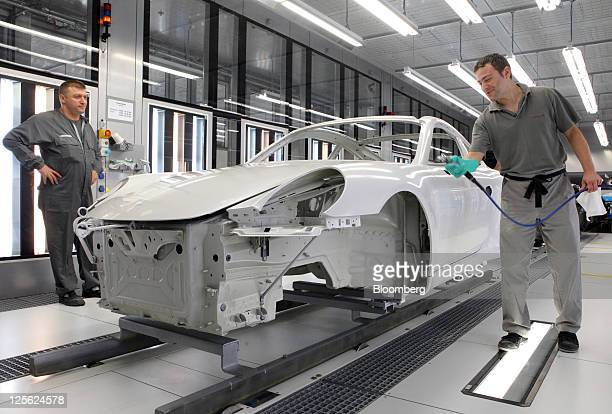 An employee cleans the body of a Porsche AG 911 automobile prior to painting at the company's new paint spraying facility in Stuttgart Germany on...