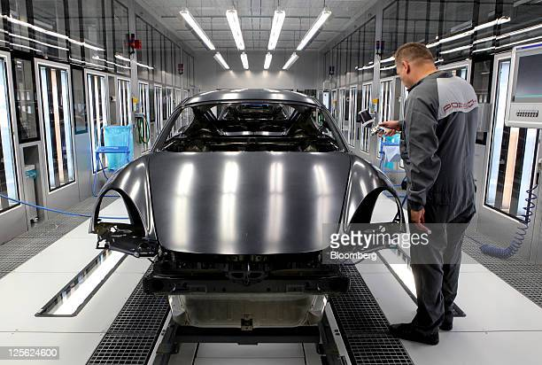 An employee cleans the body of a Porsche AG Cayman automobile prior to painting at the company's new paint spraying facility in Stuttgart Germany on...