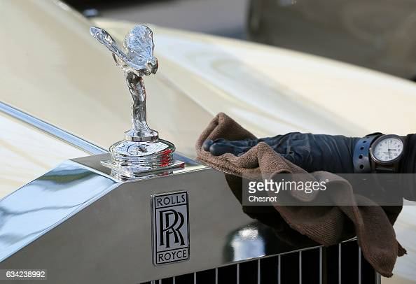 An employee cleans the famous RollsRoyce mascot 'The Spirit of Ecstasy' during a press preview before a mass auction of vintage vehicles organised by...