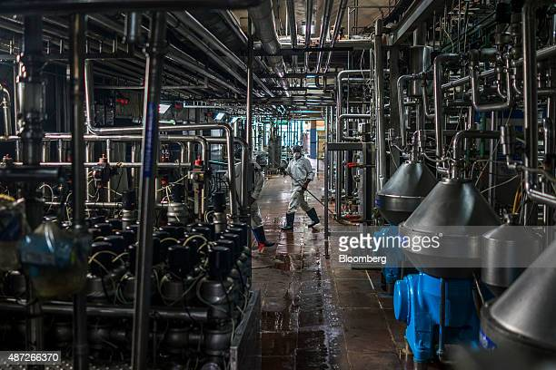 An employee cleans the floor in the automated pasteurizer unit of the Mother Dairy Pty milk plant in New Delhi India on Friday Aug 28 2015 With...