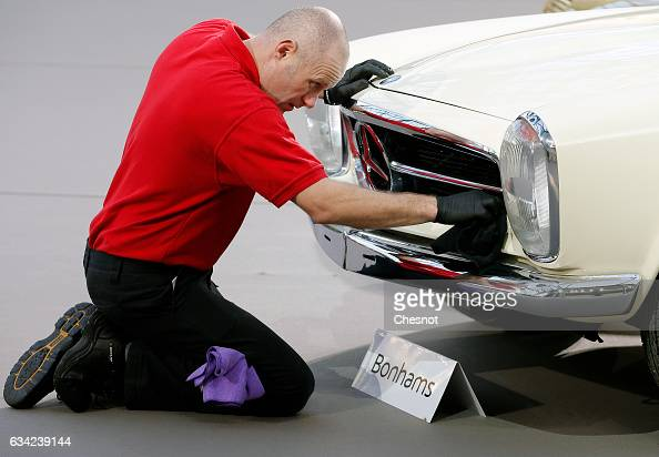 An employee cleans the front grille of a MercedesBenz model during a press preview before a mass auction of vintage vehicles organised by Bonhams...