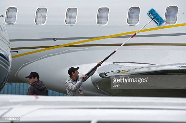 An employee cleans the fuselage of a Bombardier's Global 6000 aircraft during the Latin American business aviation fair being held in Sao Paulo...