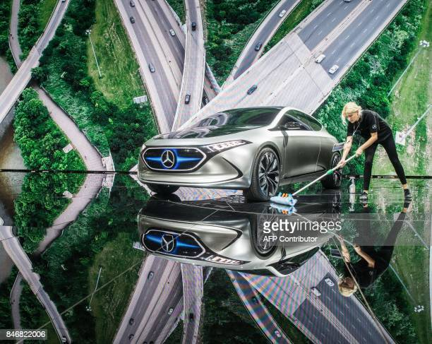 An employee cleans the ground around an electric concept car EQ A at the booth of Mercedes prior to the visit of the German Chancellor during her...