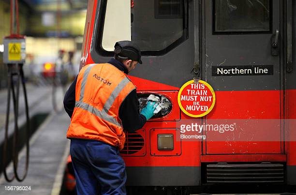 An employee cleans the headlight of a London Underground Northern Line train at Alstom SA's Traincare Centre in the Golders Green district of London...