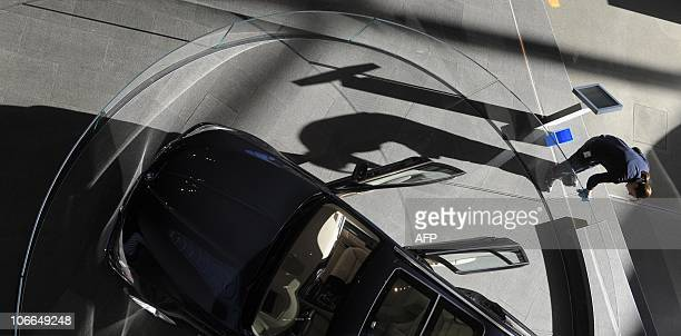 An employee cleans the presentation platform of a car by German luxury car maker BMW at the 'BMW World' delivery center near the company's...