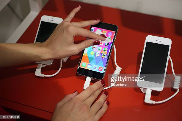 An employee cleans the screen of an Apple Inc iPhone 6S Plus displayed inside a Telekom Srbija AD mobile phone store in Belgrade Serbia on Wednesday...
