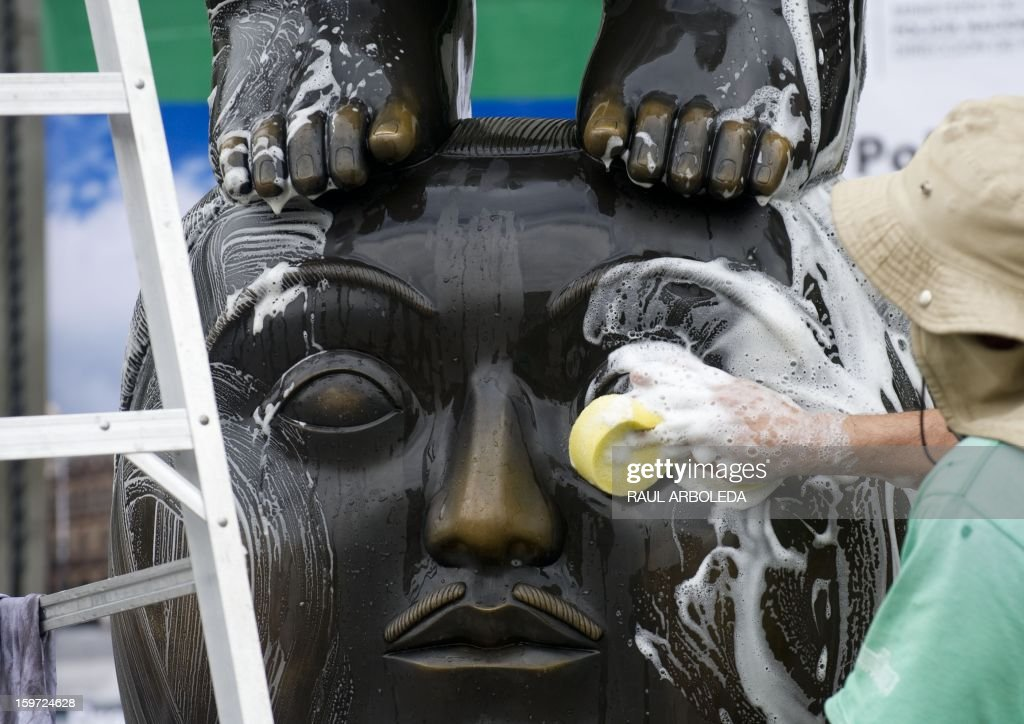 An employee cleans the sculpture 'Pensamiento' by Colombian artist Fernando Botero, in Medellin, Antioquia Department, on January 19, 2013. Each year the Antioquia museum leads a cleanup day of the 23 sculptures displayed at Botero square. AFP PHOTO/Raul ARBOLEDA