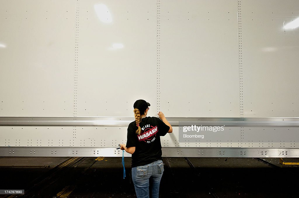 An employee cleans the side of a semi trailer prior to installation of decals at the Wabash National Corp. facility in Lafayette, Indiana, U.S., on Monday, July 22, 2013. Wabash National Corp. is scheduled to release earnings figures on July 30. Photographer: Daniel Acker/Bloomberg via Getty Images