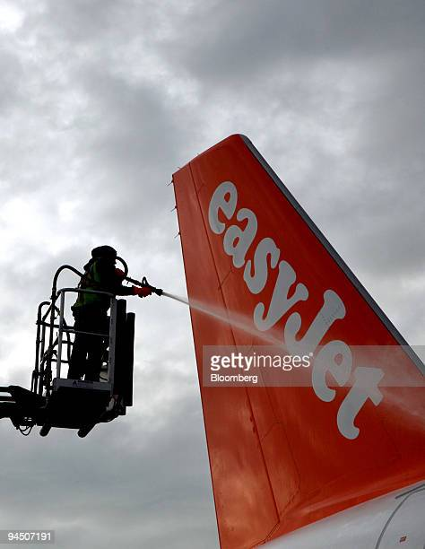 An employee cleans the tail of an EasyJet airplane at Gatwick airport in Crawley UK on Wednesday Dec 16 2009 EasyJet Plc Europe's secondbiggest...