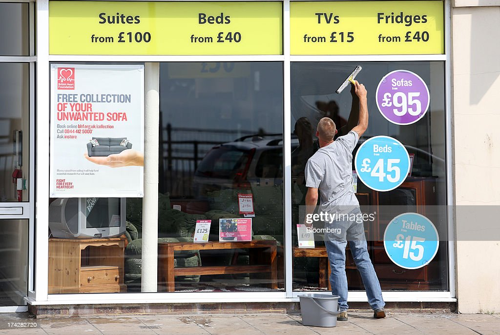 An employee cleans the window of a discount furniture and electrical appliances store in Hastings, U.K., on Tuesday, July 23, 2013. U.K. retail sales rose for a second month in June as discounts at department stores drove demand for clothes and electrical products. Photographer: Chris Ratcliffe/Bloomberg via Getty Images