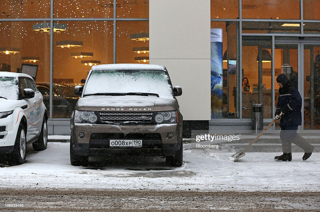 An employee clears snow near a Range Rover test automobile parked outside the entrance to a Jaguar Land Rover auto dealership in Moscow, Russia, on Thursday, Dec. 27, 2012. Tata Motors Ltd.'s Jaguar Land Rover luxury unit signed a letter of intent with Saudi Arabia's government to study the feasibility of setting up a factory to build its models locally. Photographer: Andrey Rudakov/Bloomberg via Getty Images