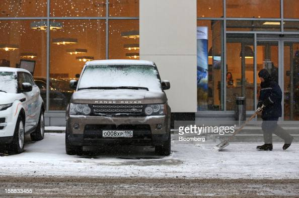 An employee clears snow near a Range Rover test automobile parked outside the entrance to a Jaguar Land Rover auto dealership in Moscow Russia on...