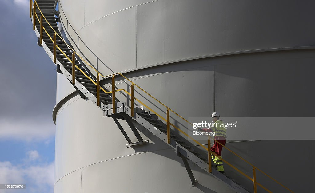 An employee climbs a staircase on the outside of a storage tank at the EON AG gas fired power station on the Isle of Grain, U.K., on Thursday, Oct. 4, 2012. The National Grid Plc and E.ON have worked together to link two plants with twin pipelines, allowing surplus heat from electricity generation at E.ON.s power station to heat LNG and convert it back to gas. Photographer: Chris Ratcliffe/Bloomberg via Getty Images