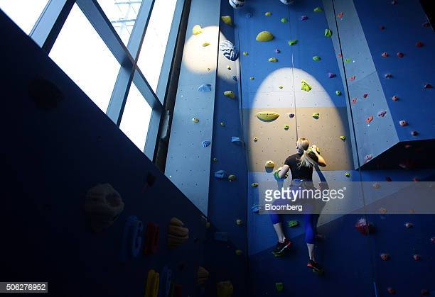 An employee climbs the rock wall in the fitness center at Google Canada's engineering headquarters in Waterloo Ontario Canada on Friday Jan 22 2016...