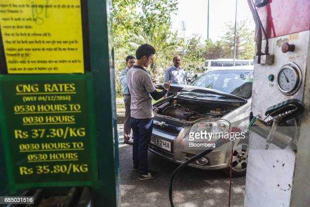 An employee closes the hood of a car after refueling it with compressed natural gas at an Indraprastha Gas Ltd gas station in New Delhi India on...