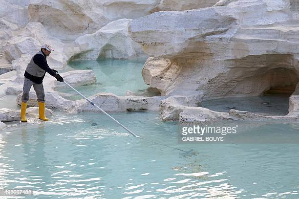An employee collect coins thrown in theTrevi fountain on November 25 2015 in central Rome The Trevi Fountain one of the main attraction for tourists...