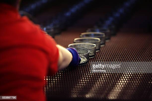 An employee collects a colored Kastehelmi style glass bowl from a conveyor belt at the Iittala Oyj glass factory operated by Fiskars Oyj in...