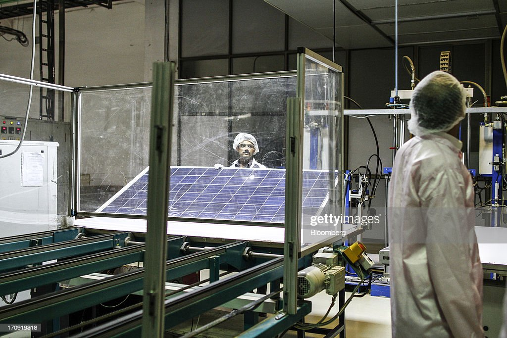 An employee collects a laminated solar panel from a module lamination machine on the solar photovoltaic module production line at the Tata Power Solar Systems Ltd. manufacturing plant in Bangalore, India, on Tuesday, June 11, 2013. Tata Groups solar unit is expanding its business building plants for customers, forecasting that offices and factories will be paying more for grid power than solar by 2016 in most Indian states. Photographer: Dhiraj Singh/Bloomberg via Getty Images