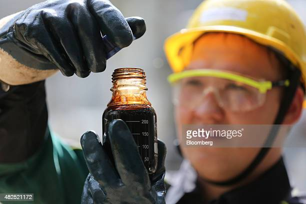 An employee collects a sample of crude oil for laboratory testing at the 'TANECO' refining and petrochemical plant operated by Tatneft OAO in...
