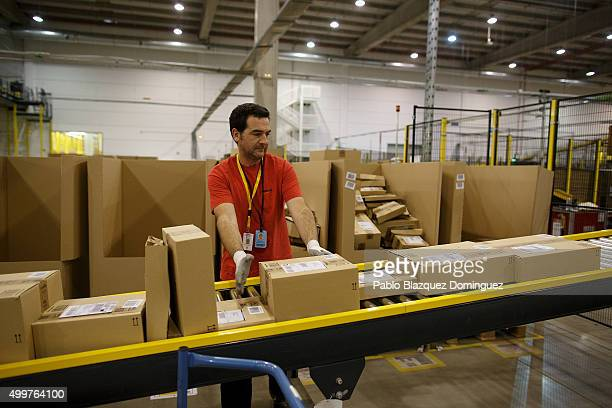An employee collects boxes from a conveyor belt at the Amazon fulfillment centre on December 3 2015 in San Fernando de Henares Madrid Spain Amazon...