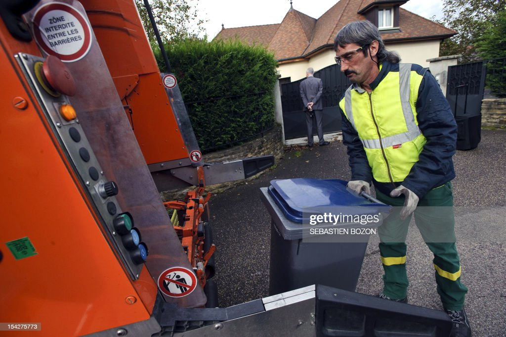 An employee collects garbage bins, on October 17, 2012 in Serre-Les-Sapins, near the French eastern town of Besancon. This 'intelligent' garbage disposal system collects waste for nearly 180,000 inhabitants in and around Besancon according to the bins' weight.