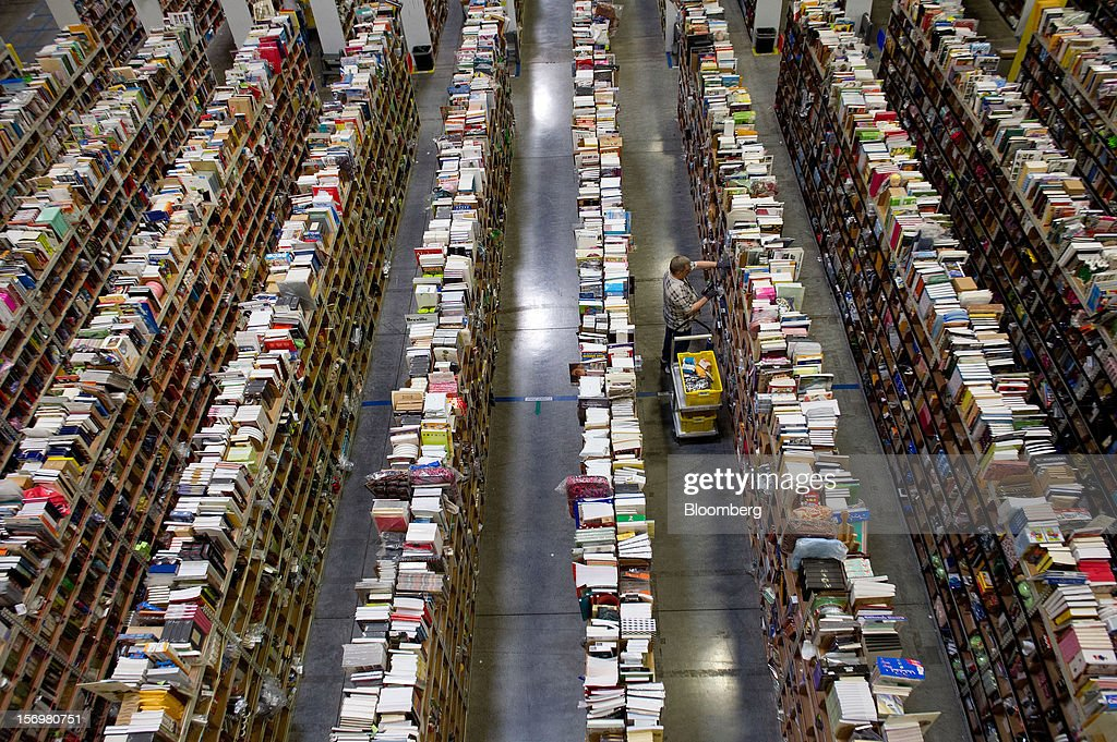 An employee collects merchandise ordered by customers for shipment from the Amazon.com distribution center in Phoenix, Arizona, U.S. on Monday, Nov. 26, 2012. U.S. retailers are extending deals into Cyber Monday and beyond to try to sustain a 13 percent gain in Thanksgiving weekend sales. Photographer: David Paul Morris/Bloomberg via Getty Images