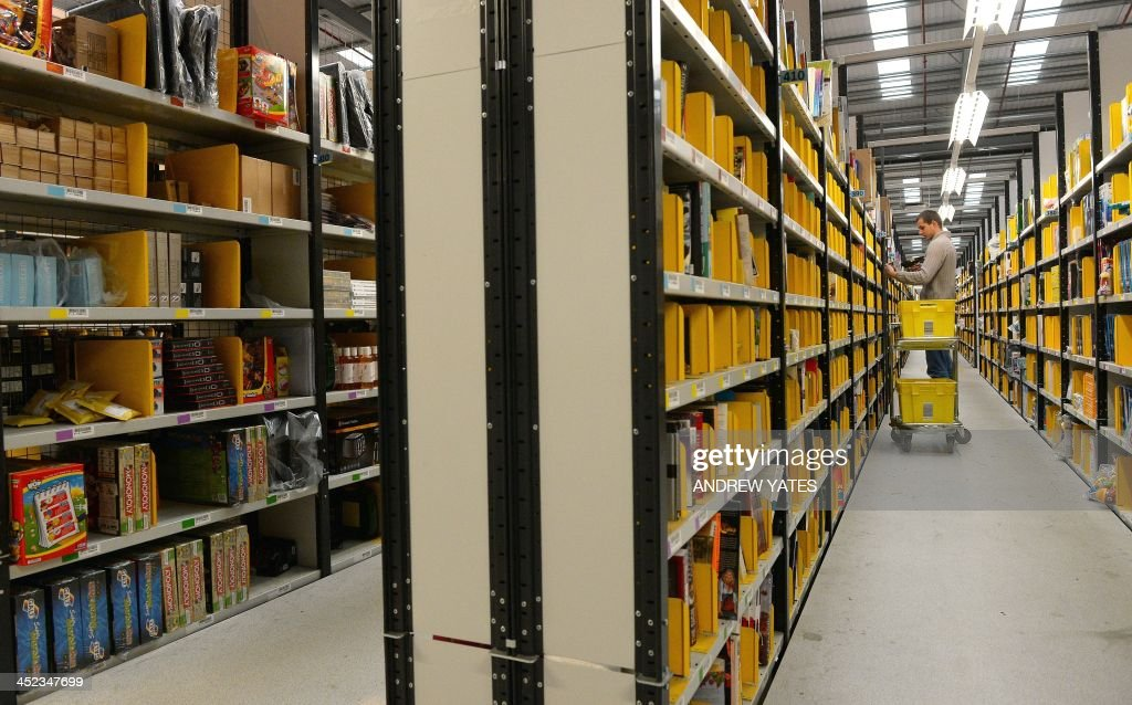 An employee collects orders at the Fulfilment Centre for online retail giant Amazon in Peterborough, central England, on November 28, 2013, ahead of Cyper Monday on December 2nd, expected to be one of the busiest online shopping days of the year. AFP PHOTO/ANDREW YATES