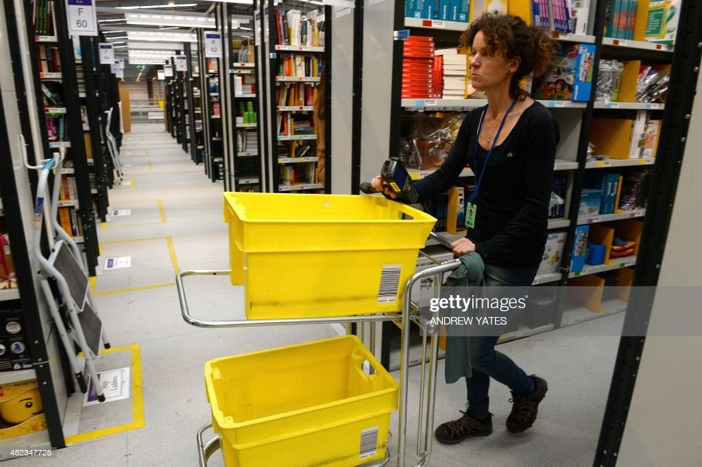 An employee collects orders at the Fulfilment Centre for online retail giant Amazon in Peterborough, central England, on November 28, 2013, ahead of Cyper Monday on December 2nd, expected to be one of the busiest online shopping days of the year.