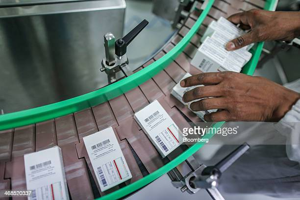 An employee collects packs of Ketoprofen tablets as they move along the production line inside the packaging unit at the Lupin Ltd pharmaceutical...