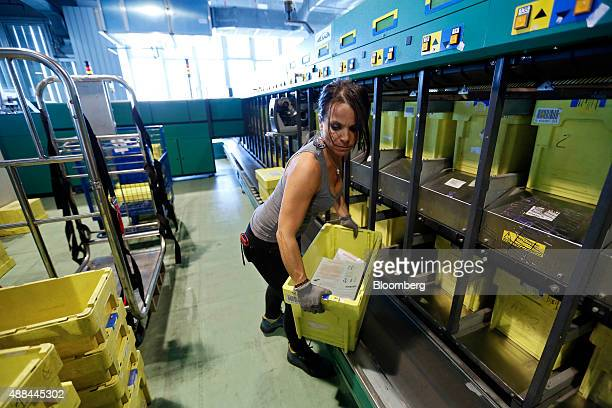 An employee collects presorted mail for delivery in crates from a sorting machine inside a Poste Italiane SpA postal sorting office in Fiumicino near...