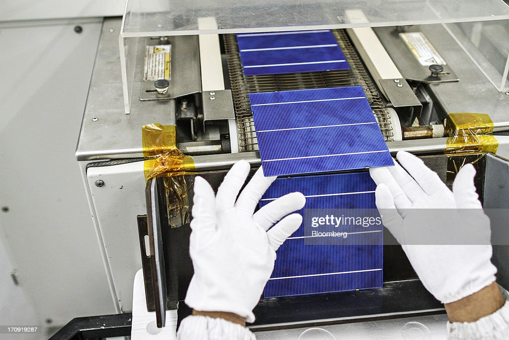 An employee collects solar cells from a busbar printing machine on the cell production line at the Tata Power Solar Systems Ltd. manufacturing plant in Bangalore, India, on Tuesday, June 11, 2013. Tata Groups solar unit is expanding its business building plants for customers, forecasting that offices and factories will be paying more for grid power than solar by 2016 in most Indian states. Photographer: Dhiraj Singh/Bloomberg via Getty Images
