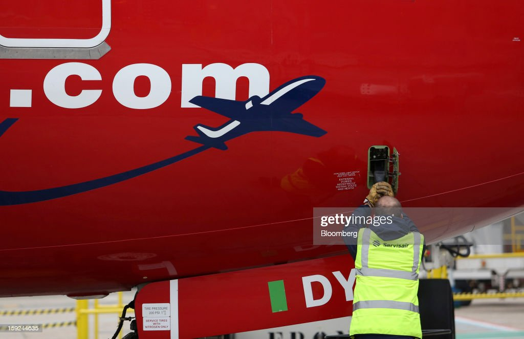 An employee connects a cable to a Boeing 737-800 aircraft, operated by Norwegian Air Shuttle AS, at Gatwick airport in Crawley, U.K., on Thursday, Jan. 10, 2013. Gatwick, acquired by Global Infrastructure Partners Ltd. in 2009 after regulators sought a breakup of BAA Ltd., owner of the larger Heathrow hub, is 30 miles (48 kilometers) south of London and serves about 200 destinations, more than any other U.K. airport, according to flight schedule data provider OAG. Photographer: Chris Ratcliffe/Bloomberg via Getty Images
