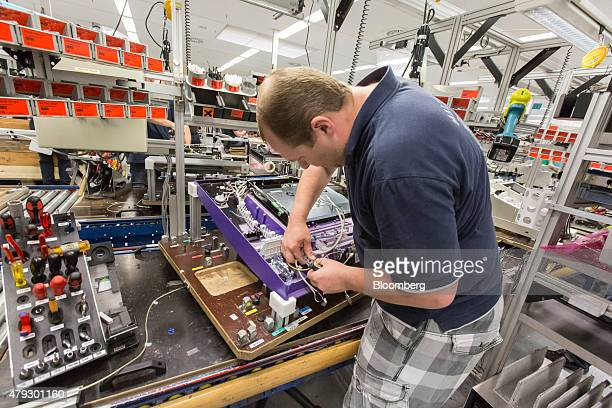 An employee connects cables beneath a key pad unit of an automated teller machine on the production line at Wincor Nixdorf AG in Paderborn Germany on...