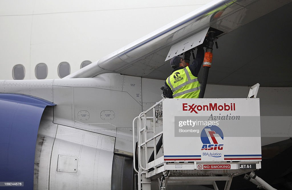 An employee connects the fuel hose from an Exxon Mobil Corp. aviation gas truck to the wing of a British Airways aircraft ahead of refueling at Gatwick airport in Crawley, U.K., on Thursday, Jan. 10, 2013. Gatwick, acquired by Global Infrastructure Partners Ltd. in 2009 after regulators sought a breakup of BAA Ltd., owner of the larger Heathrow hub, is 30 miles (48 kilometers) south of London and serves about 200 destinations, more than any other U.K. airport, according to flight schedule data provider OAG. Photographer: Chris Ratcliffe/Bloomberg via Getty Images