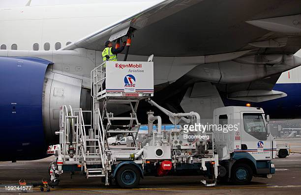 An employee connects the fuel hose from an Exxon Mobil Corp aviation gas pumping truck to the wing of a British Airways aircraft ahead of refueling...