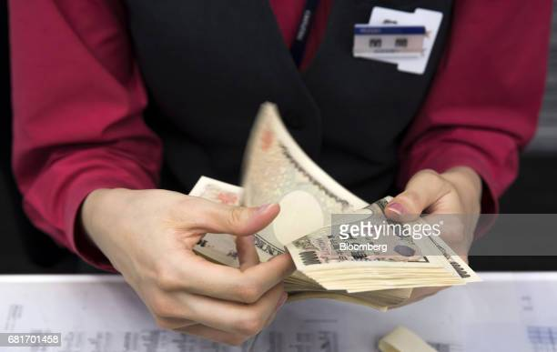An employee counts 10000 yen banknotes at the Mizuho Bank Ltd branch inside the Mizuho Financial Group Inc headquarters in Tokyo Japan on Friday...