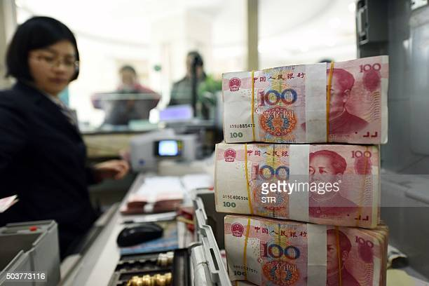 An employee counts 100yuan banknotes at a bank in Lianyungang in eastern China's Jiangsu province on January 7 2016 China weakened the value of its...