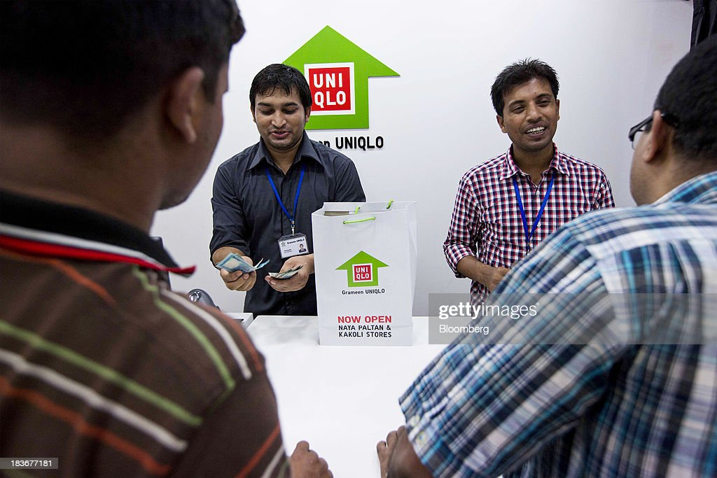 An employee counts Bangladeshi taka banknotes at the cash register at the opening of a Grameen Uniqlo store, a joint venture between Fast Retailing Co. and Grameen Healthcare Trust, in the Paltan area of Dhaka, Bangladesh, on Saturday, Oct. 5, 2013. Fast Retailing, Asia's biggest clothing retailer, set up the venture with Grameen Healthcare Trust to design, make and sell clothes in Bangladesh. Photographer: Jeff Holt/Bloomberg via Getty Images