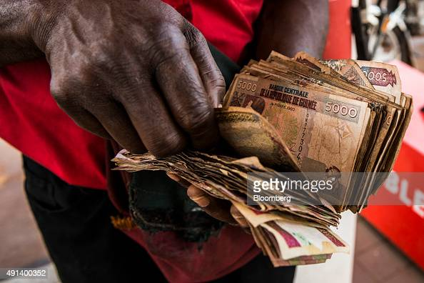 An employee counts Guinean franc banknotes on the forecourt of a gas station operated by Total SA in Kamsar Guinea on Monday Sept 7 2015 With 43...
