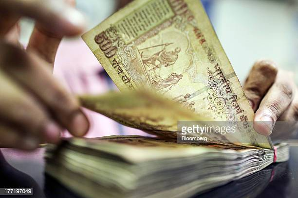 An employee counts Indian fivehundred rupee banknotes for a photograph at a branch of the HDFC Bank Ltd in Mumbai India on Thursday Aug 22 2013...